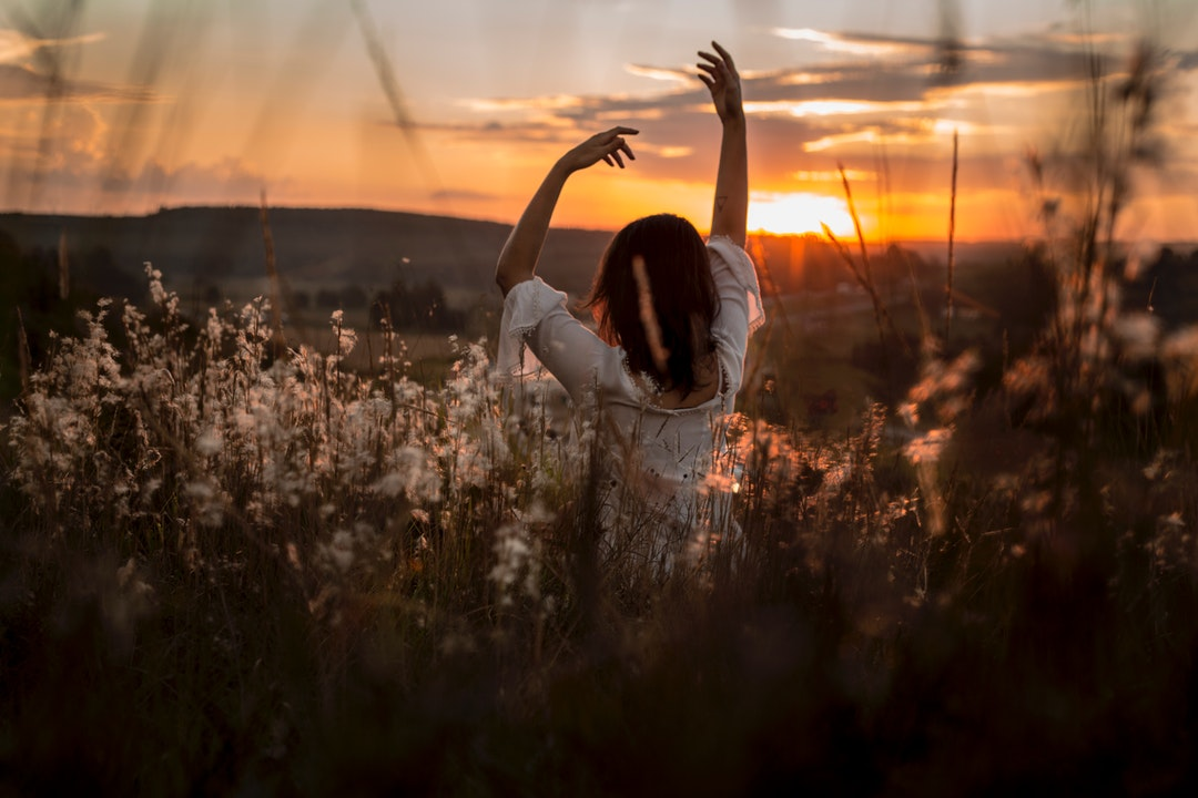 Brunette woman doing a yoga pose inside long grass in Curitiba at sunrise