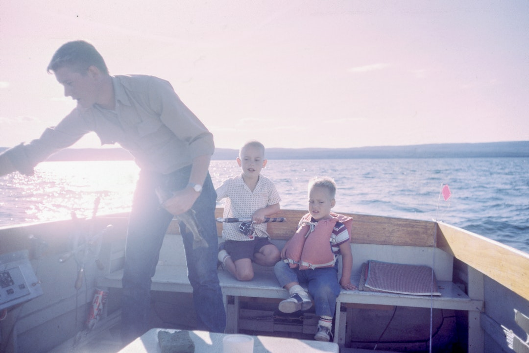 Violet hues overtake photo of a father fishing with his two young sons on a boat