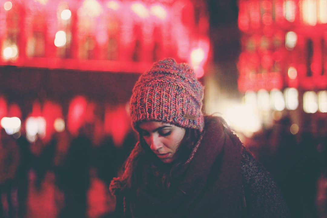 A woman in a knit cap looks down against red lights at the Grand Palace