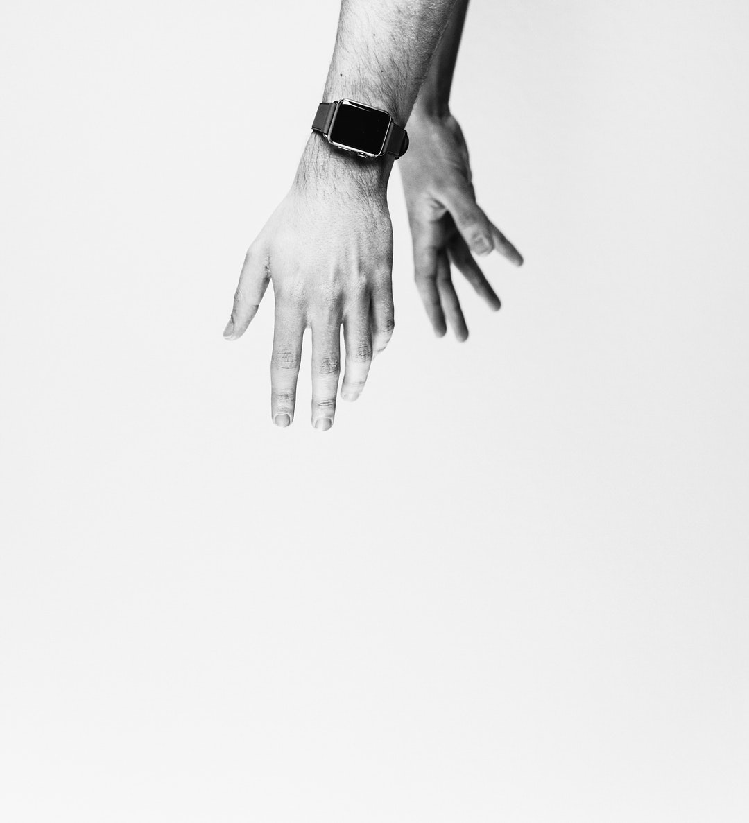 The hands of a person wearing an Apple Watch in black and white