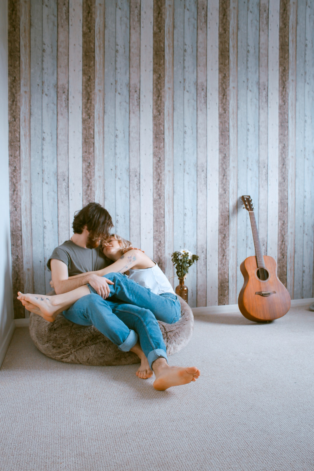 A barefooted man and woman cuddle on a beanbag chair against wood paneling, near a guitar