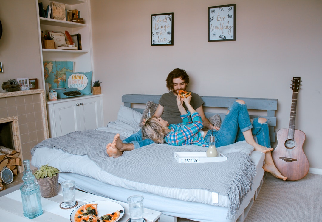 Young couple on bed feeding each other pizza with fireplace, guitar and wall art in teddington