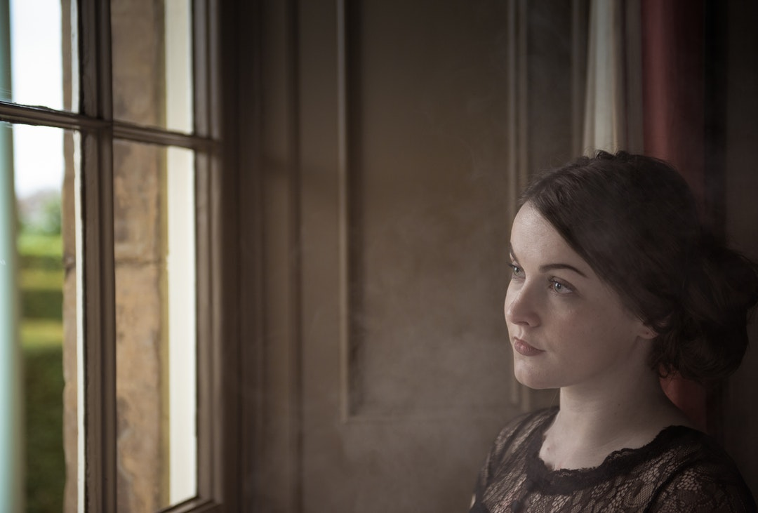 A young woman with brown, pulled-back hair looks out a window
