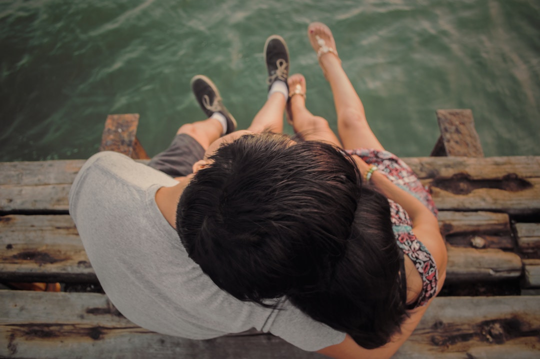 Young woman and her boyfriend pictured sitting on a dock with their legs dangling