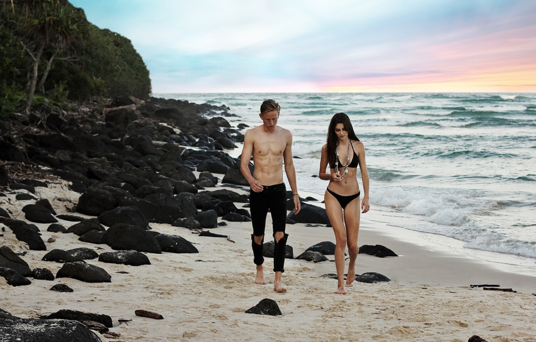 Couple in swimsuits walking on the sand beach