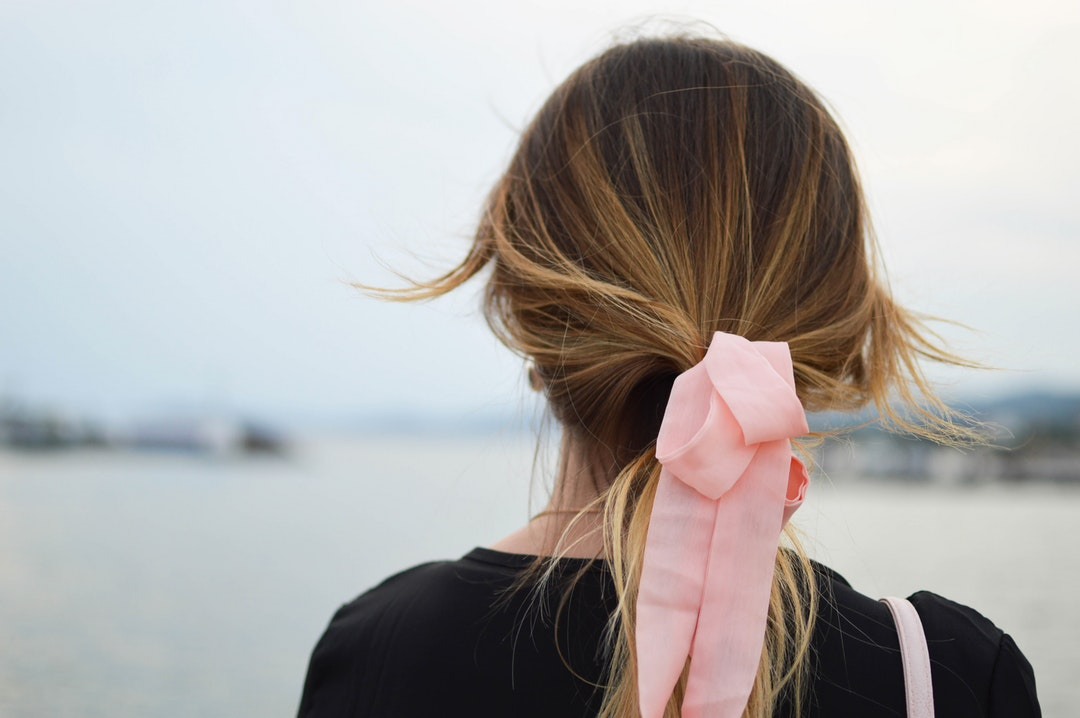 focus photography of woman with pink hair bow facing on body of water