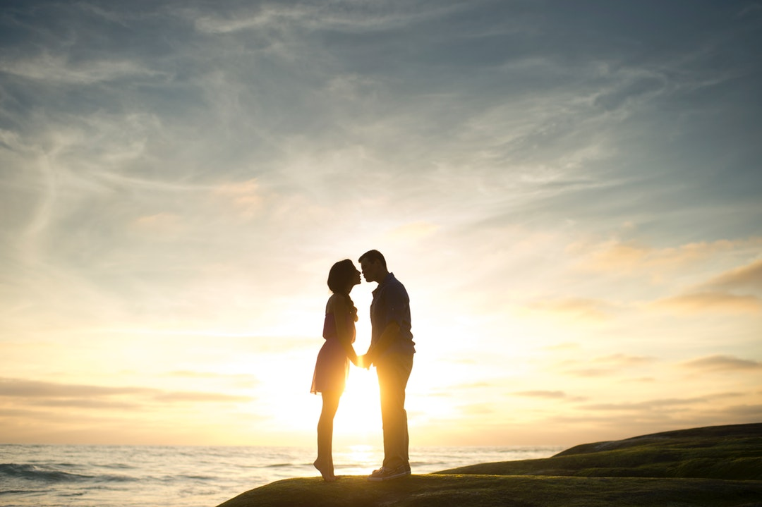 A couple in silhouette kisses on a rock overlooking a sunset by the ocean