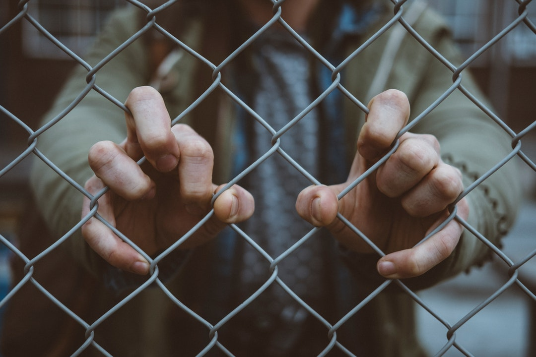 Macro view of an urban person's hand on a chain link fence in De Nieuwe Stad