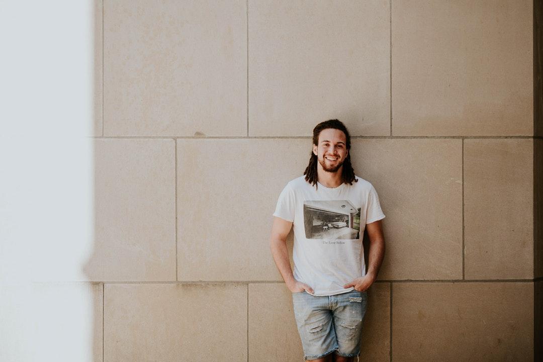 A man wearing a t-shirt and denim cutoff shorts