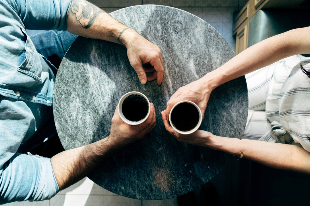 Two people holding cups of coffee while seated opposite to each other at a round table