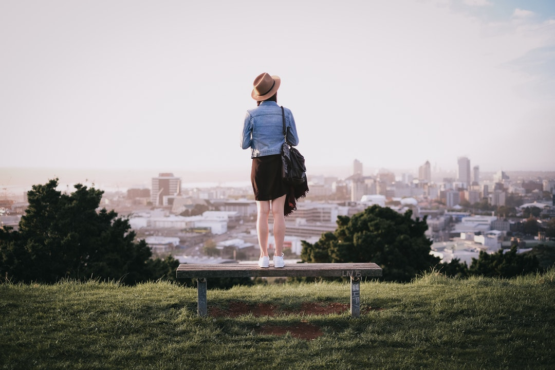 Woman standing on a park bench and surveying the city below