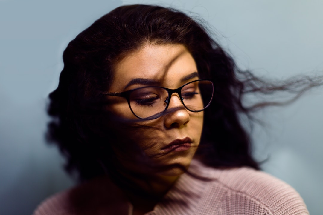 Serious woman in glasses shaking out curly hair