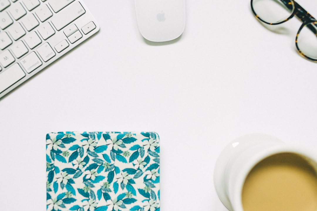 An overhead shot of a keyboard, a mouse, a pair of glasses, a cup of coffee and a coaster on a white surface