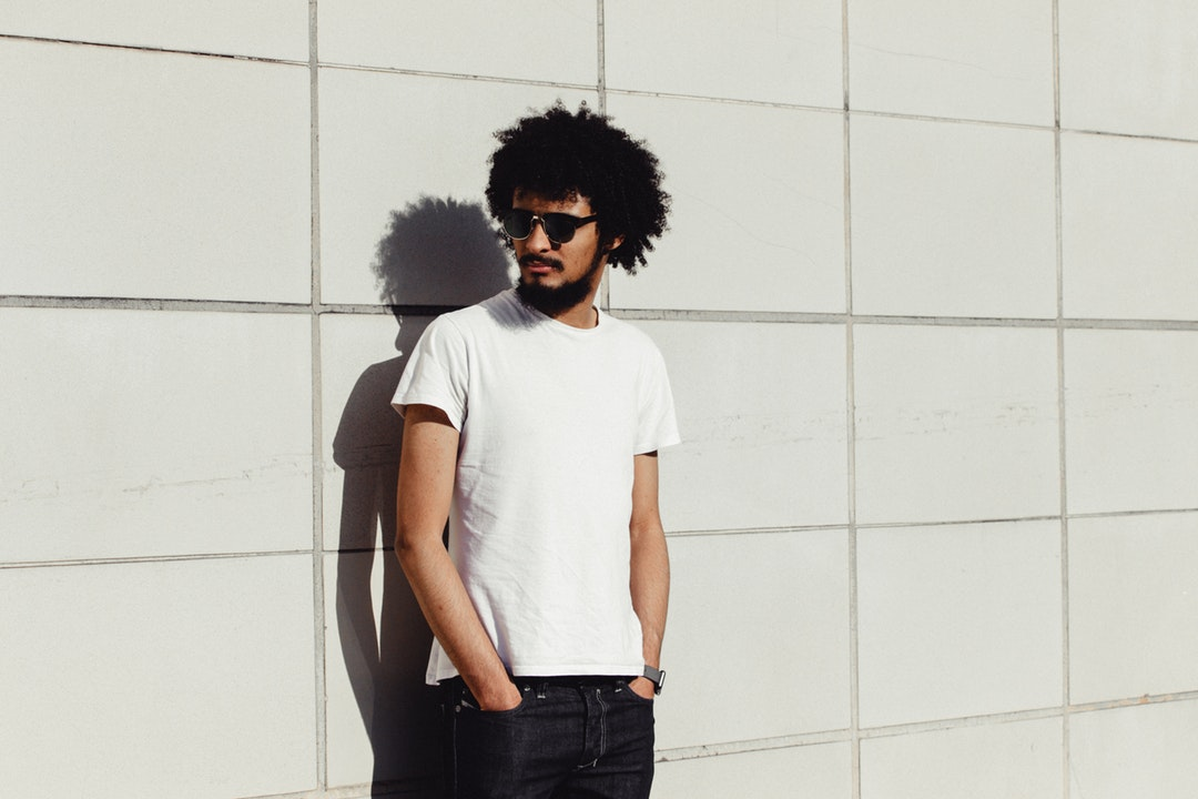 Man with curly hair wearing sunglasses standing against a wall