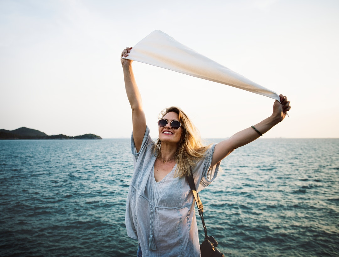 A woman wearing sunglasses holding up a white flag by the sea