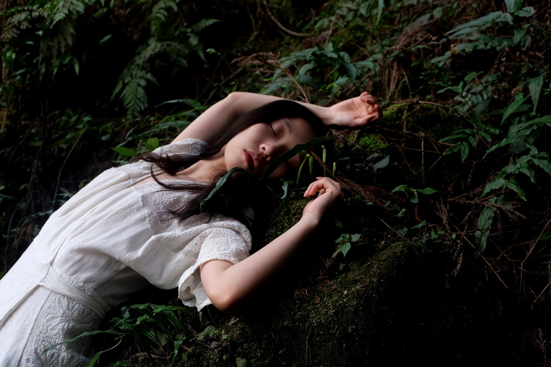 A young woman in a lace dress sleeping on the forest floor