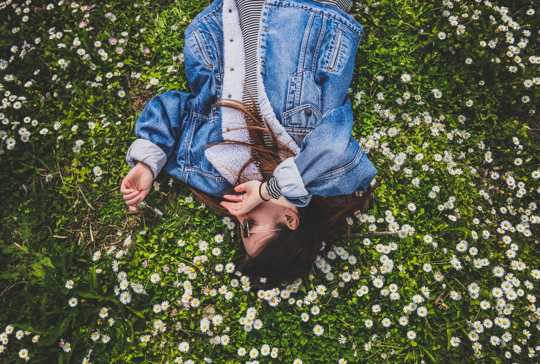 Happy woman laying down in a field of wildflowers