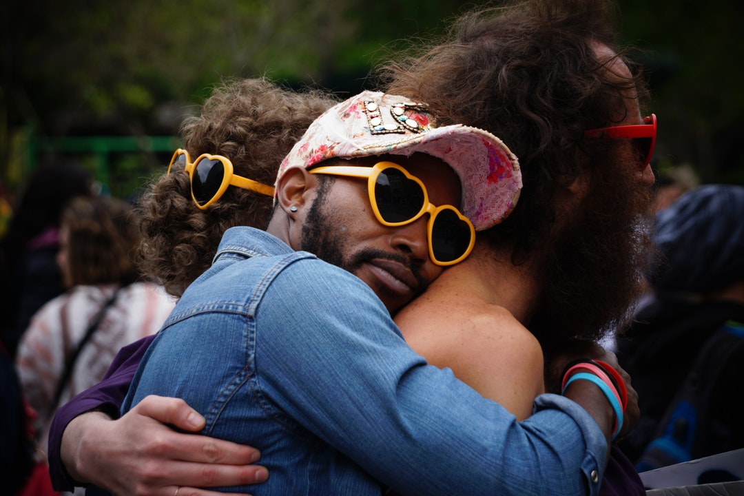 Group hug between men of different races wearing heart-shaped sunglasses