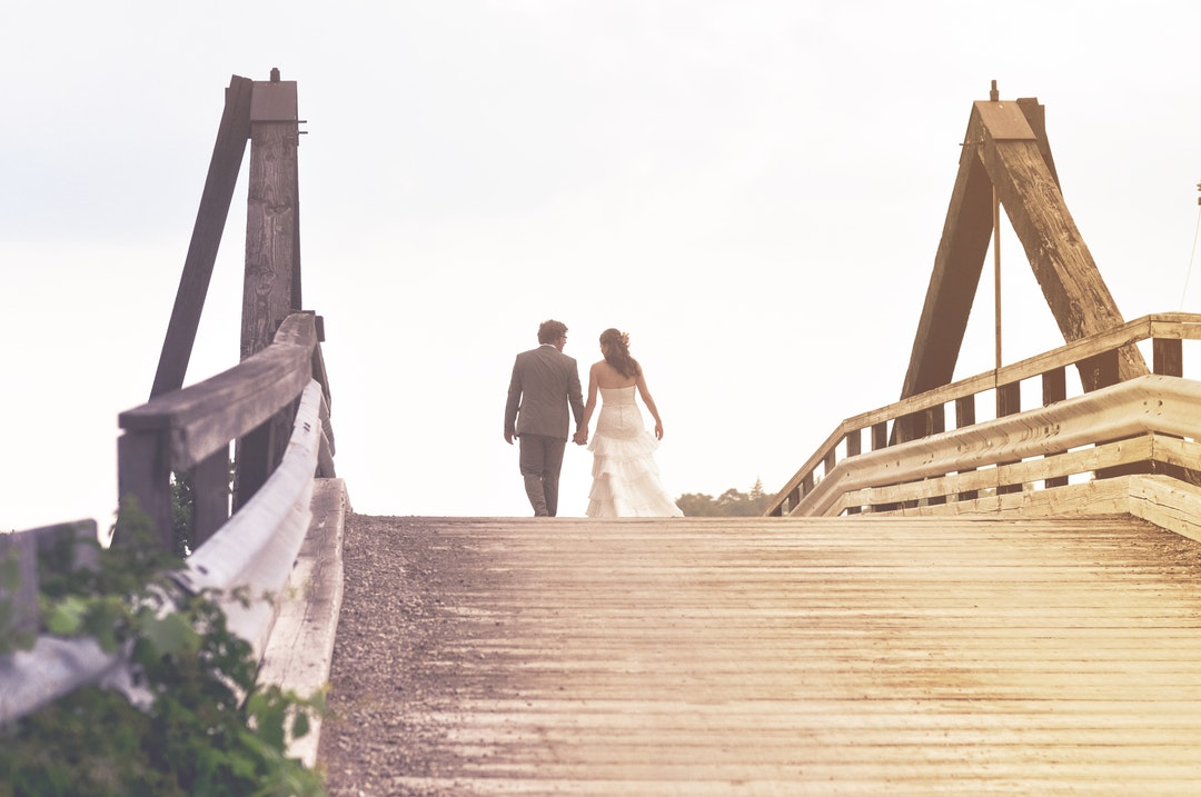 A man and woman in wedding attire are walking on a bridge in London.