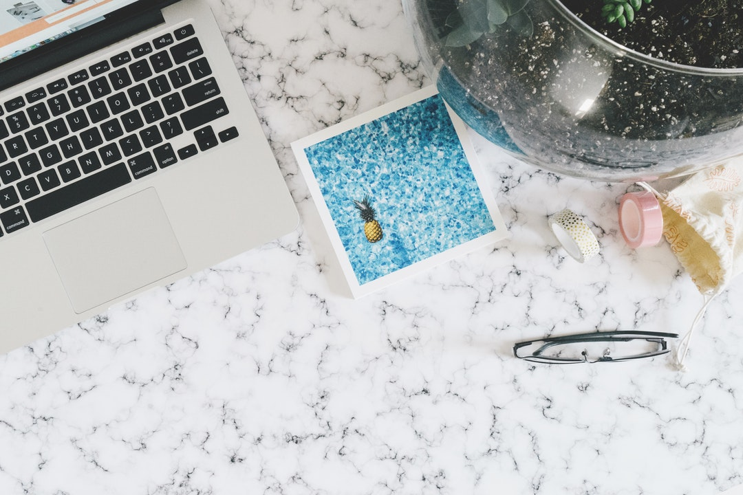 A Macbook and other items on top of a marble table.