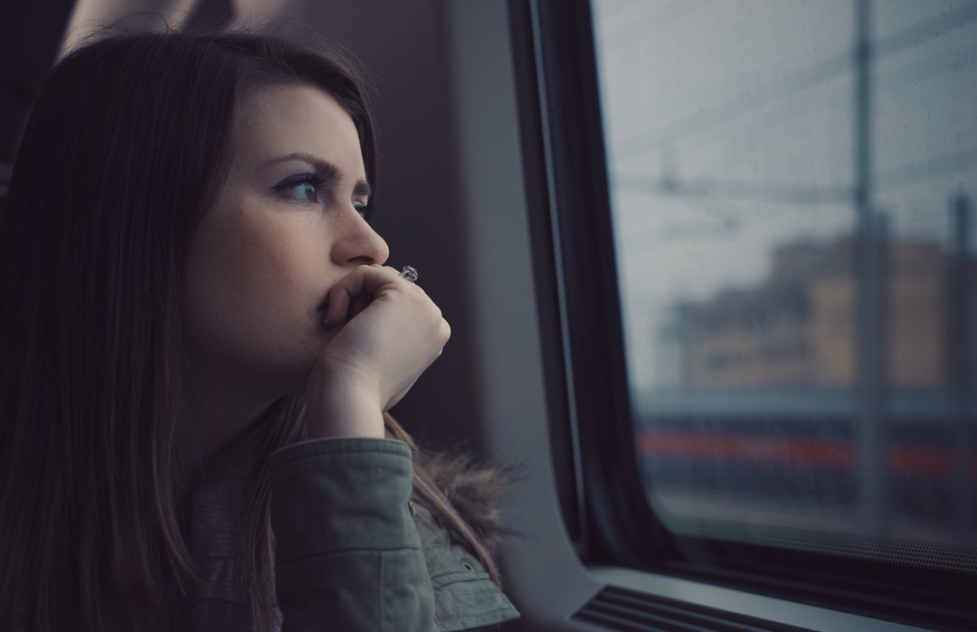 Thinking woman looking out a train car window alone