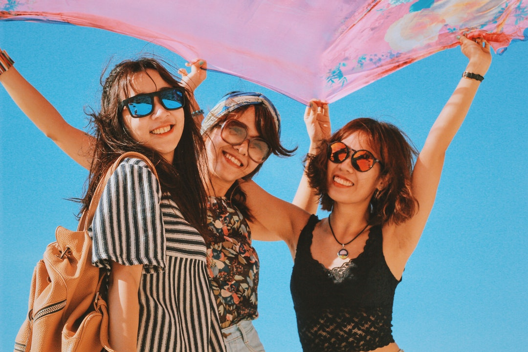 Three smiling women in glasses hold up a large pink scarf in Lý Sơn