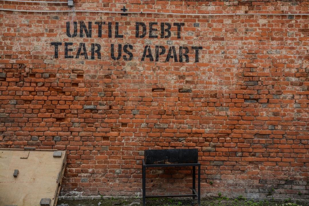 """Graffiti on an old brick wall reads """"until debt tear us apart"""""""