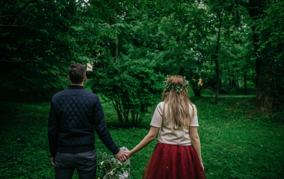 Couple wearing whimsical forest outfits holding hands