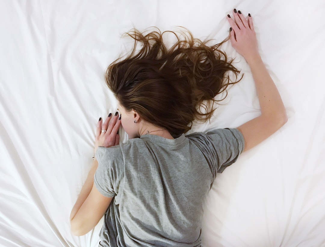 A woman with brown hair and a gray t-shirt lies face down on a white sheet