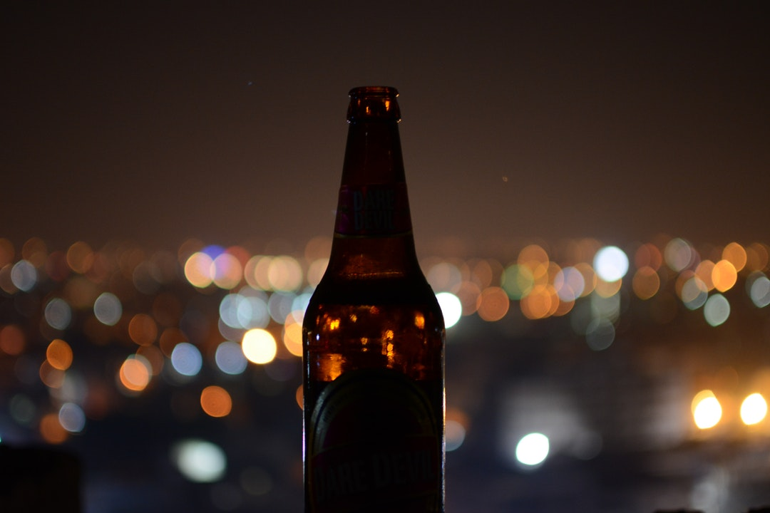 Macro view of a brown dare devil beer bottle in silhouette with blurry city lights behind it