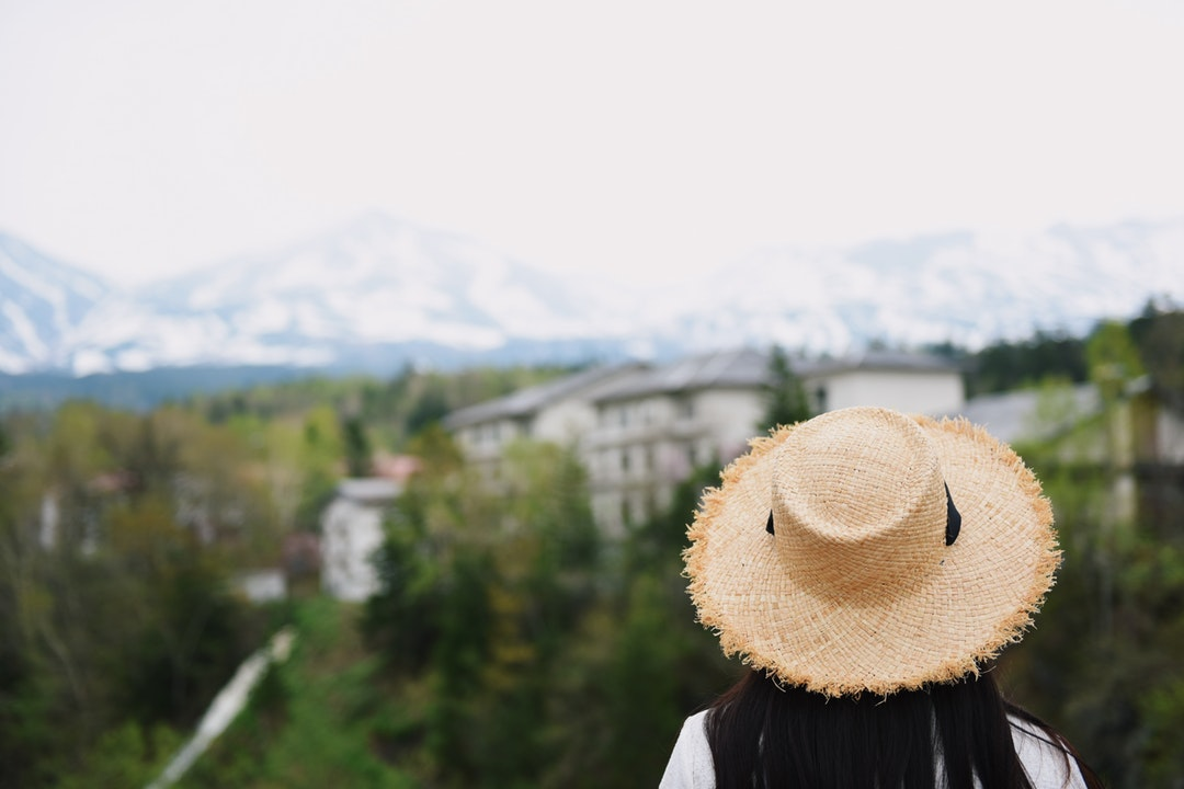 A woman with dark hair wearing a straw hat looking at a village surrounded by trees under a snowy white mountain