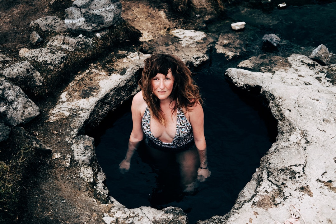 Woman in a swimsuit standing in a natural hot spring