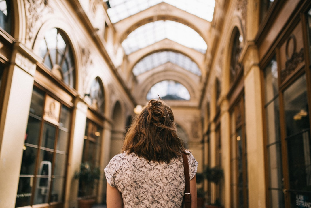 A fashionable young woman in a tunnel with a glass ceiling