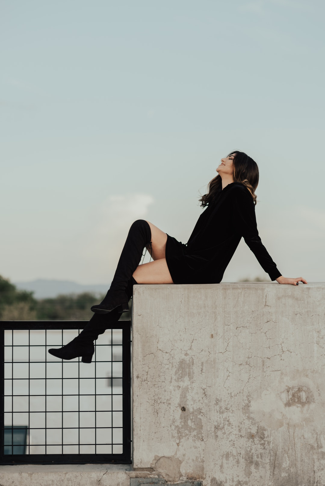 An attractive woman in a black dress with black knee high socks and high heel footwear sits posed on a cement wall in Salt Lake City