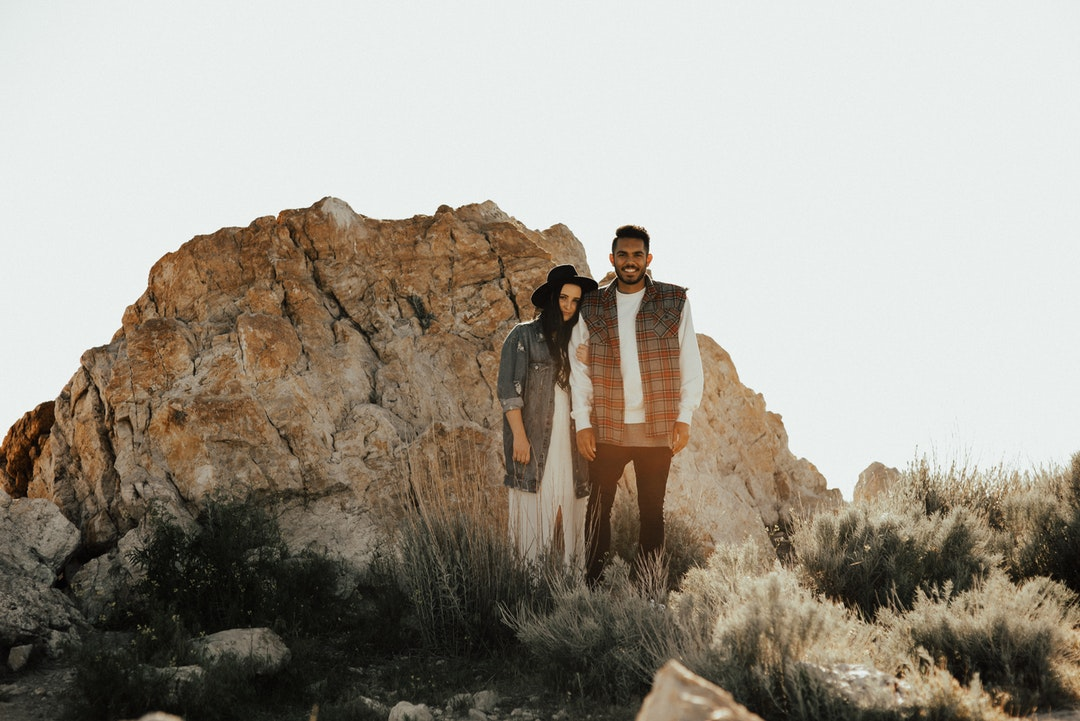 A man and woman stand close in front of large rock at dusk