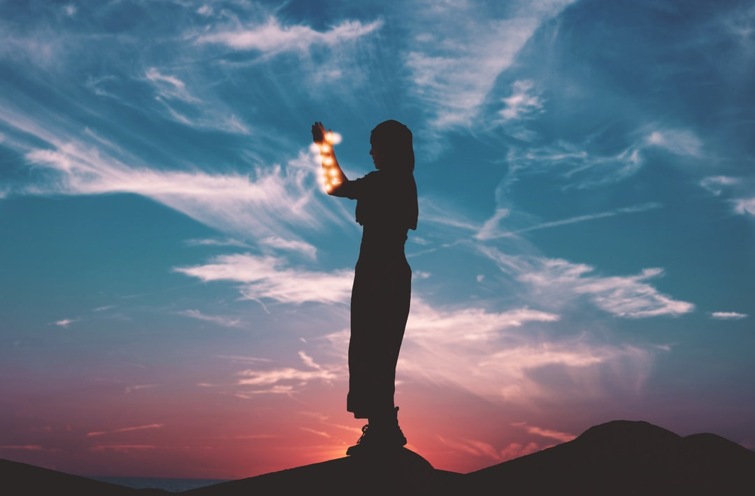 A silhouette woman holding lights stands in front of a blue and red twilight sky backdrop