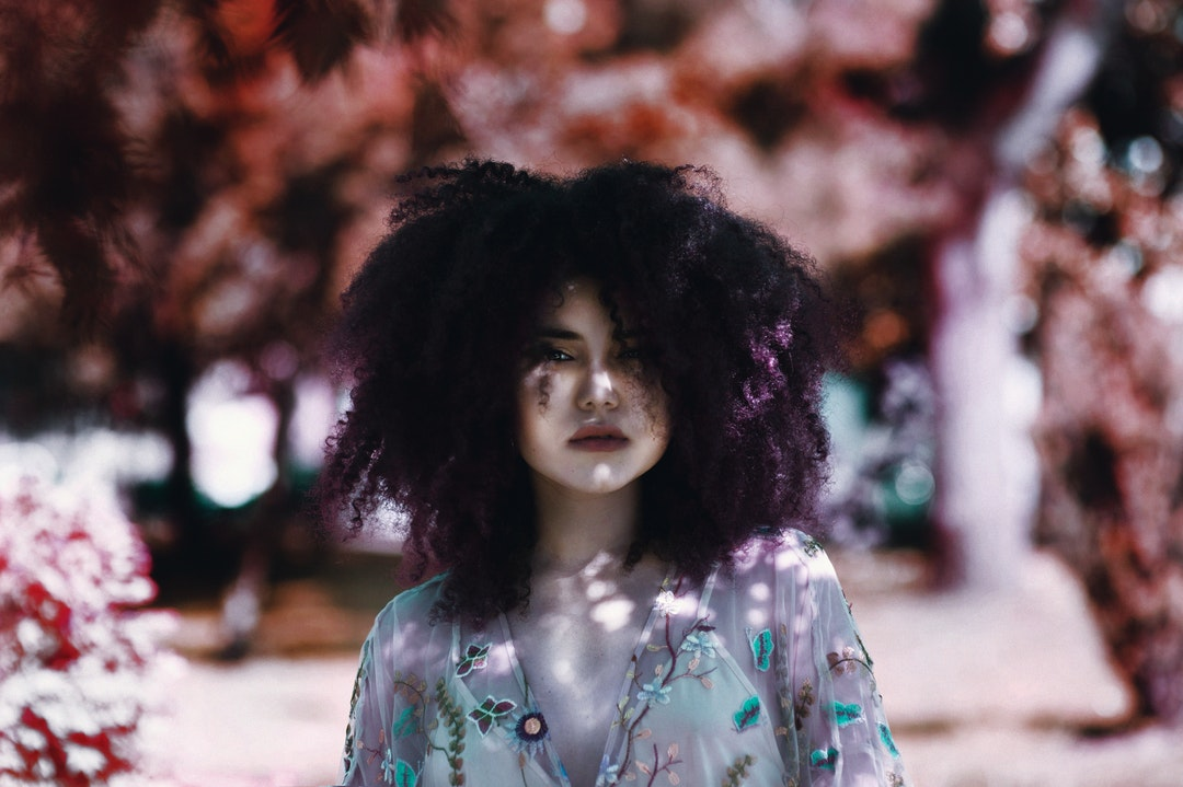 A woman with purple-tinted curly hair in a sheer top stands before a blurry outdoor background