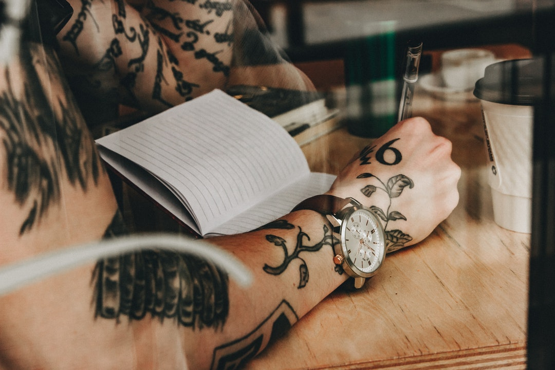 Milwaukee man with tattoos wearing wristwatch writing in journal while sitting at cafe