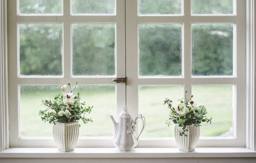 A porcelain teapot between two potted plants on a windowsill
