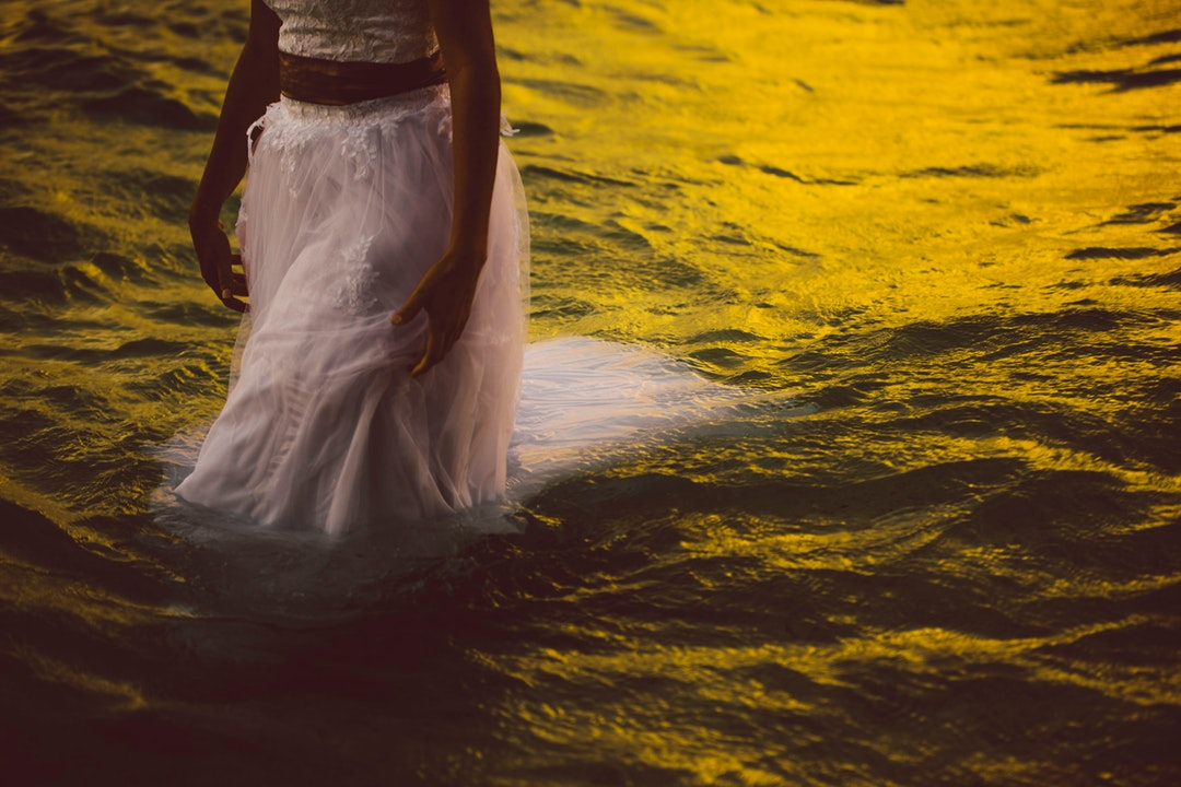 A woman walking in the sea in a white dress, as the water reflects the Rarotonga sunset