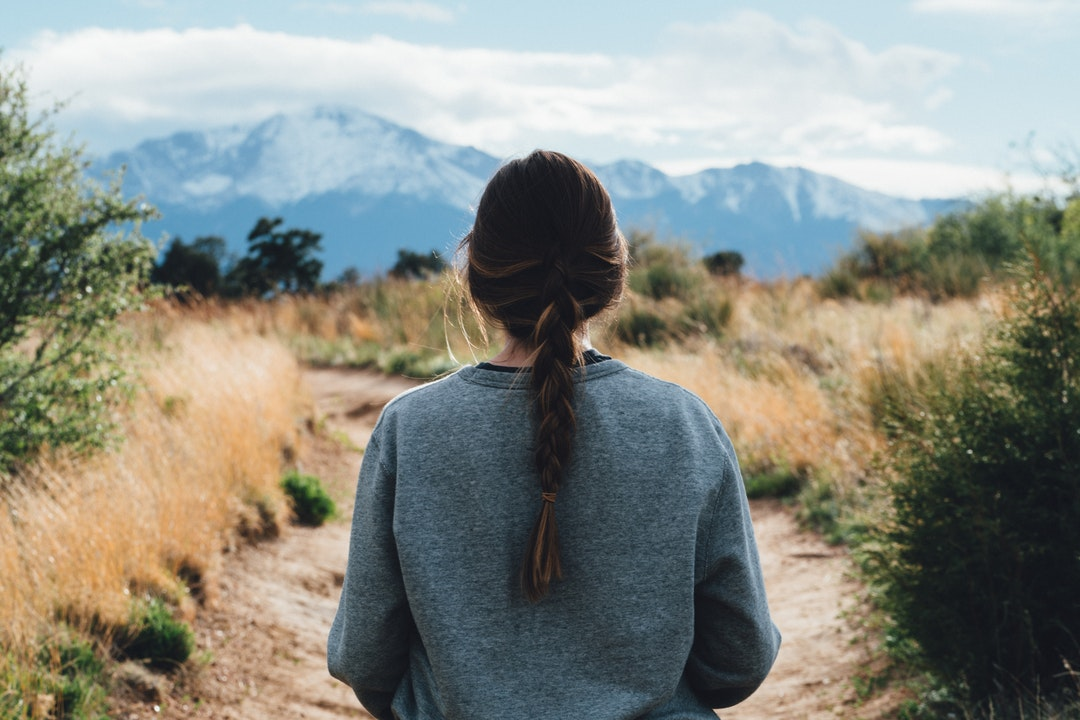Standing behind a woman with braided hair near mountains