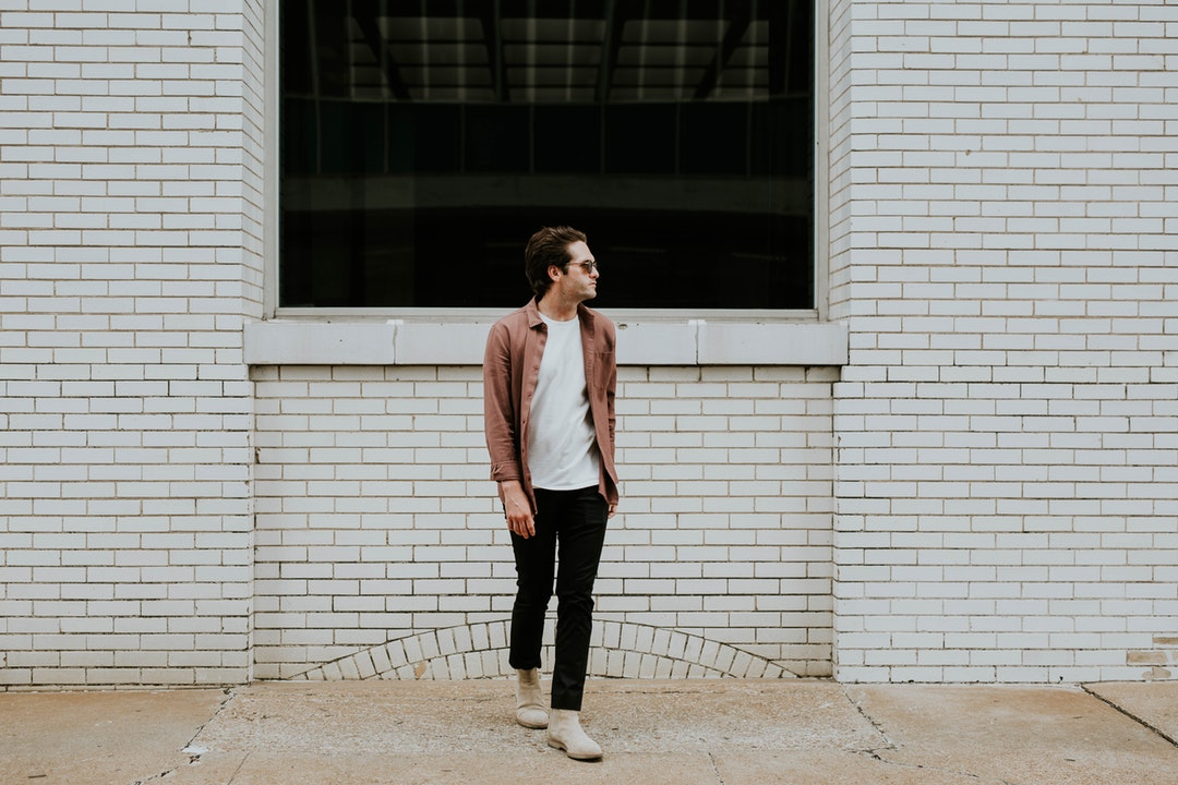 A man wearing sunglasses looks to the side in front of a white brick wall