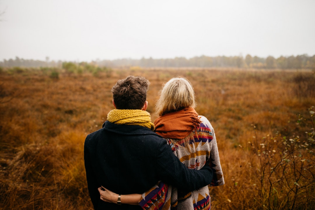 couple standing on brown grass field near tall trees at daytime