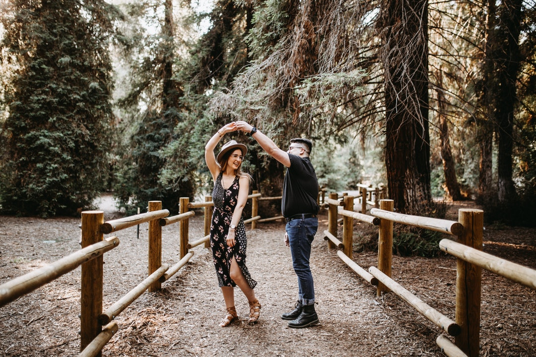 A man and a woman dance, holding hands, on a fenced-in pathway in the woods