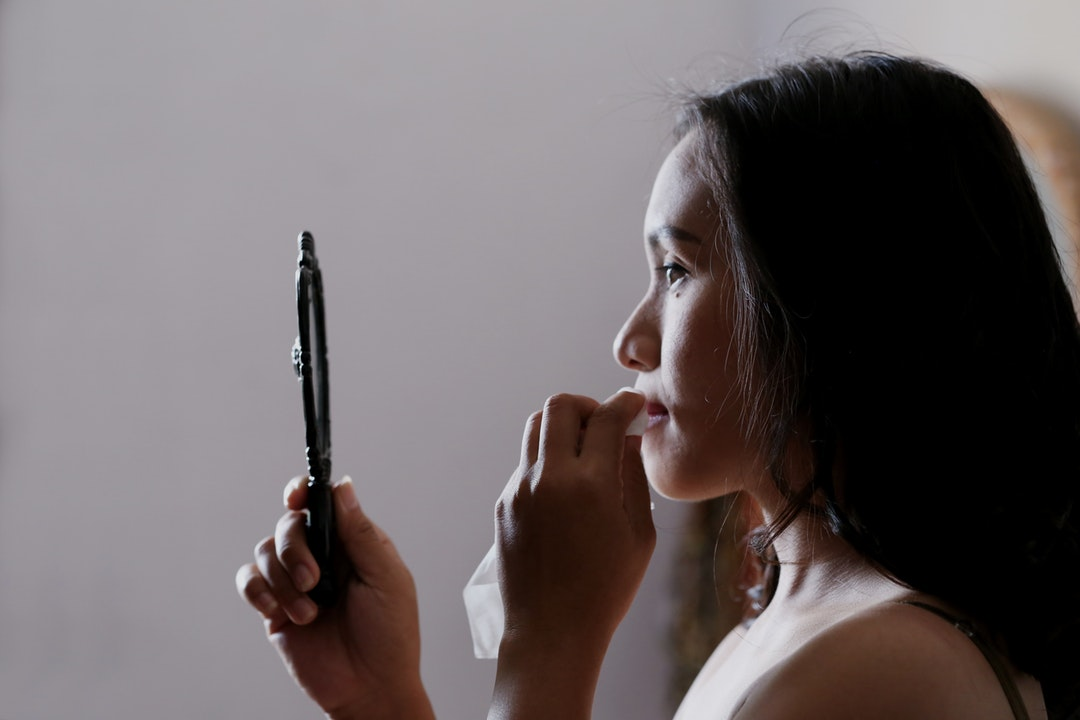 A woman dabs her mouth with a napkin while holding a hand mirror in Bekasi.