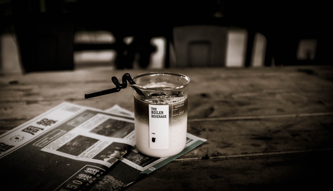 Coffee in a beaker with a straw on a newspaper