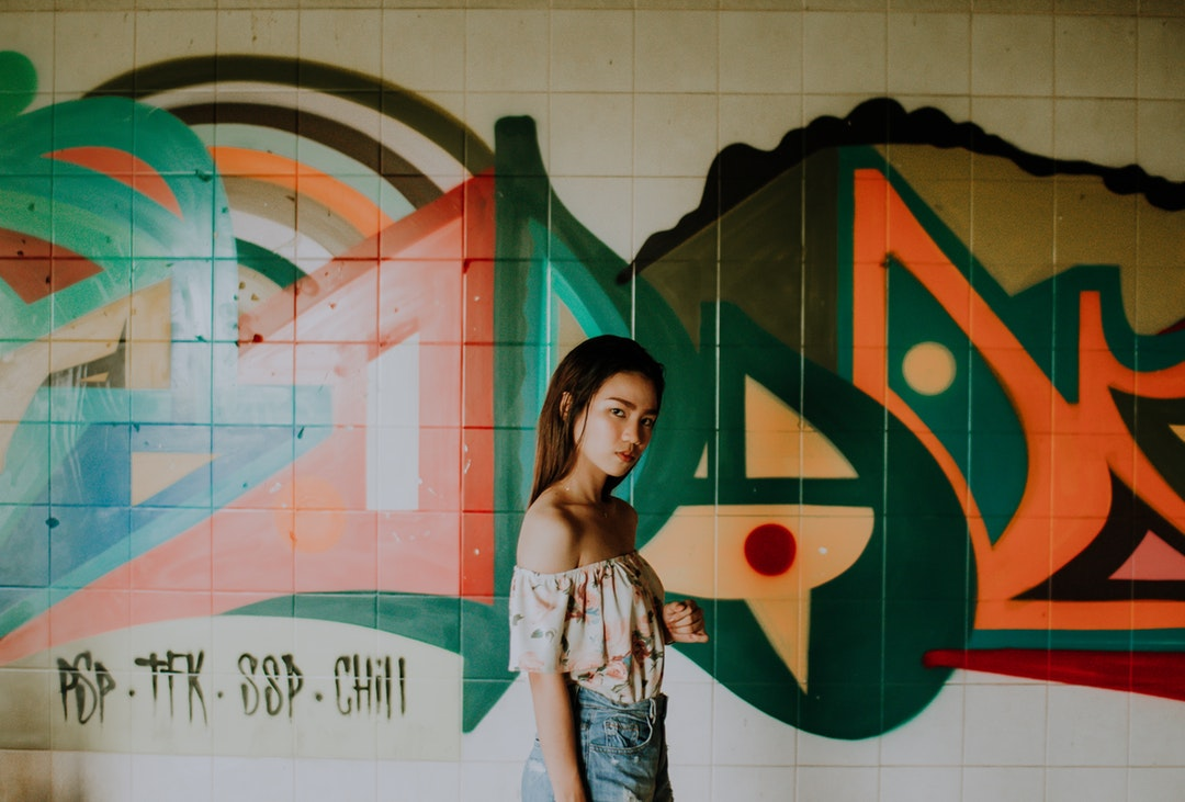 A young woman in an off-shoulder top looks at the camera against a graffiti wall.