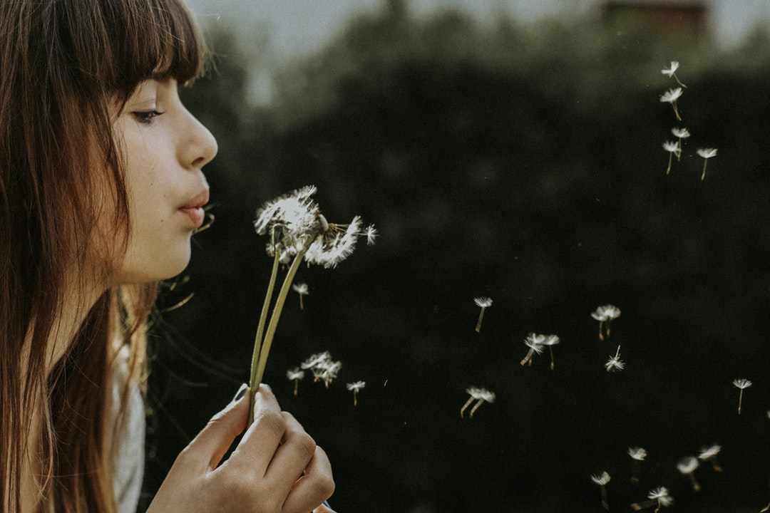 A woman with bangs blows on a dandelion, scattering its seeds
