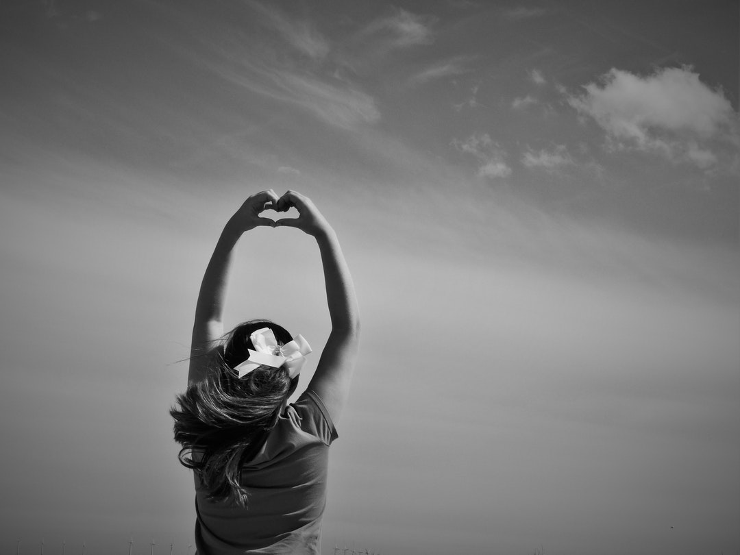 A black-and-white shot of a woman holding up her hands and forming a heart shape with her fingers