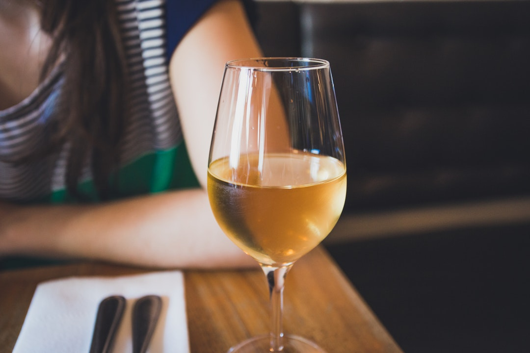 A macro view of a wine glass with white wine in it in Larrys